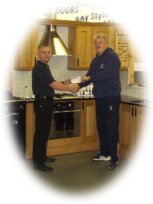 Sponsor - HTM Products - Jon Knapp hands over the cheque to Mac McCran in front of one of his display kitchens